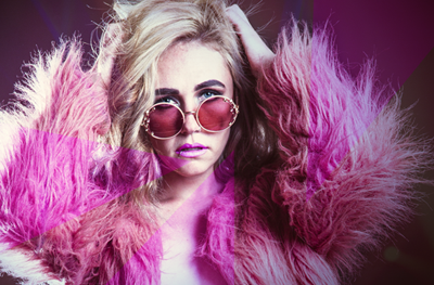 A beautiful white blonde woman wearing a pink fur coat and a pair of sunglasses